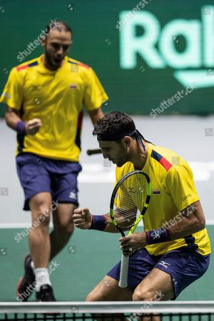 Colombia players Robert Farah, foreground and Juan Sebastian Cabal celebrate a point during their Davis Cup tennis double match against Belgium Sander Gille and Joran Vliegen in Madrid, Spain