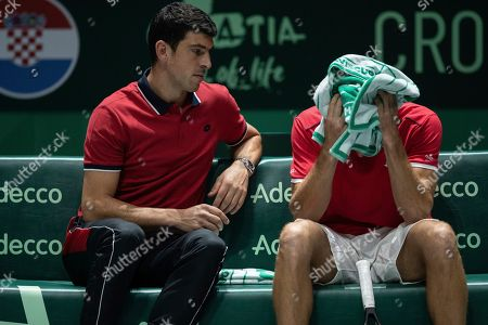 Stock Image of Croatia's team's captain Franko Skugor, left, talks with teammate Borna Gojo during their Davis Cup tennis match against Russia's Andrey Rublev in Madrid, Spain