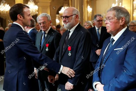 French President Emmanuel Macron (L) awards Robert Hue (C) former mayor of Montigny-les-Cormeilles, with Chevalier of the Legion of Honour (Legion d'honneur) at the Elysee Palace in Paris, France, 18 November 2019.