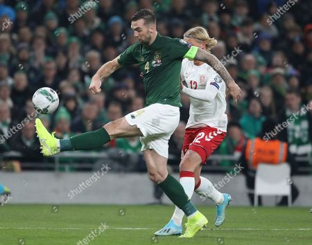 Ireland's Shane Duffy, left, clears the ball under pressure from Denmark's Kasper Dolberg during the Euro 2020 group D qualifying soccer match between Ireland and Denmark at the Aviva stadium in Dublin, Ireland