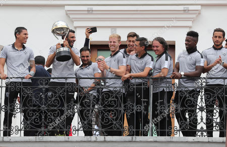 """Efren Mera, captain of Ecuador's Independiente del Valle soccer team, rises the Copa Sudamericana 2019 trophy accompanied by teammates at the government palace in Quito, Ecuador. The team was awarded by President Lenin Moreno with the medal """"National Order for Merits"""
