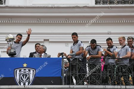 Efren Mera (L) player of Independiente del Valle soccer team waves holding the trophy of Copa Sudamericana tournament accompanied by President of Ecuador Lenin Moreno (2-L) and teammates from the balcony of the Governement Palace in Quito, Ecuador, 18 November 2019. Moreno decorates Independente del Valle following their Copa Sudamericana 2019 win.
