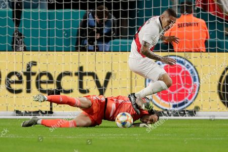 Colombia goalkeeper David Ospina makes a save as Peru forward Paolo Guerrero looks on during the first half of an international friendly soccer match, in Miami Gardens, Fla