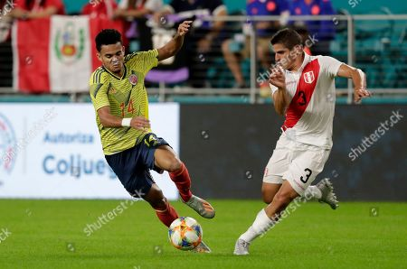 Stock Image of Colombia forward Luis Díaz (14) goes for the ball as Peru defender Aldo Corzo (3) defends during the first half of an international friendly soccer match, in Miami Gardens, Fla