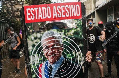 "An anti-government protester holds his shield adorned with a portrait of the Chile's President Sebastian Pinera inside a bull's eye, during clashes with police in Santiago, Chile, . The text on the shield reads in Spanish ""Murderous Sate"