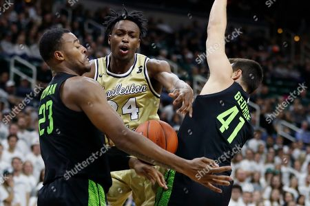 Stock Picture of Phlandrous Fleming Jr., Xavier Tillman, Conner George. Charleston Southern guard Phlandrous Fleming Jr. (24) is defended by Michigan State forward Xavier Tillman (23) and guard Conner George (41) during the first half of an NCAA college basketball game, in East Lansing, Mich