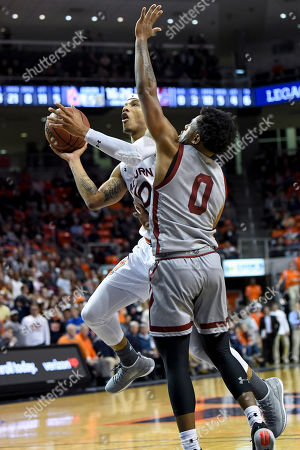 Auburn guard Samir Doughty (10) scores defended by Colgate guard Nelly Cummings (0) during the second half of an NCAA college basketball game, in Auburn, Ala