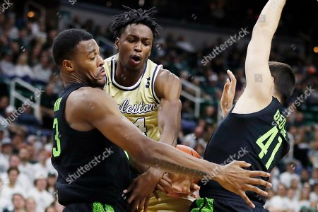 Charleston Southern guard Phlandrous Fleming Jr. (24) is defended by Michigan State forward Xavier Tillman (23) and guard Conner George (41) during the first half of an NCAA college basketball game, in East Lansing, Mich