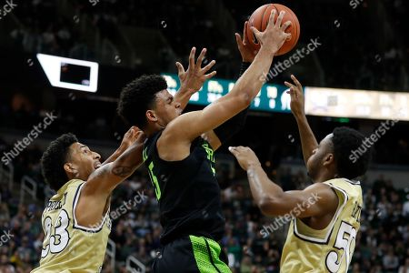 Michigan State forward Malik Hall grabs a rebound next to Charleston Southern guards Sean Price (23) and Malik Battle during the second half of an NCAA college basketball game, in East Lansing, Mich