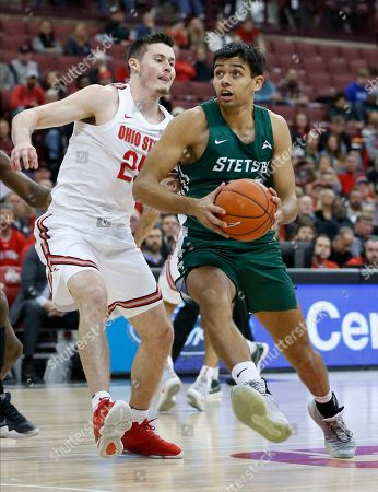 Stetson's Cyriaque Foucart, right, drives to the basket as Ohio State's Kyle Young defends during the first half of an NCAA college basketball game, in Columbus, Ohio