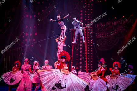 """Artists from Colombia and Japan perform """"Icarian Games"""" act on the 6th China International Circus Festival in Zhuhai, Guangdong Province, China, 17 November 2019 (issued 19 November 2019). Zhuhai is a coastal city in Guangdong, Province, China. Also known as a Chinese Riviera just opposite to Macau. Borders Hong Kong to the east and Macau to the west. It is one of China's first Special Economic Zones. The world?s longest sea-crossing bridge, Hong Kong-Zhuhai-Macau bridge has become essential for coordinating innovative developments in cities of the Greater Bay Area. In one year nearly 500 new Macao enterprises were registered in Zhuhai's Hengqin Free Trade Zone. Zhuhai due location and neighboring cities start to attract more visitors with its entertainment business such as China International Circus Festival. China International Circus Festival is considered one of the top venues and the best-paid circus festivals in the world. First time held in 2013 and completed five successful seasons, attracted 45 countries circus playing teams, 134 boutique?s spectacular shows. The Monte-Carlo International Festival, also considered as a world-class festival will present shows in Zhuhai this year.  A total of 24 circus troupes and 200 performers from 22 countries will participate in the 6th China International Festival. Visitors can enjoy watching aerial acrobatics, extreme sports, magic shows and clowns in the Chimelong International Circus City.The design of the Chimelong International Circus City has been inspired by the story of The Lord of The Rings. A large circular LED screen has been embedded in the silver façade of the theater which looks like a diamond ring, adding a variety of modern effects offers a new visual experience."""