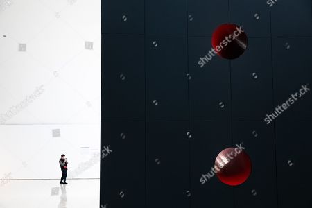 A visitor takes photos of 'Sectional Body preparing for Monadic Singularity' artwork during an exhibition of British-Indian artist Anish Kapoor, at the CAFA Art Museum, in Beijing, China, 19 November 2019. The first solo museum show in China for Anish Kapoor presents his most significant works and runs until 01 January 2020.