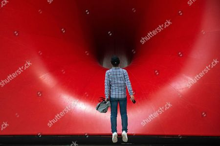 A visitor jumps to look at 'Sectional Body preparing for Monadic Singularity' artwork during an exhibition of British-Indian artist Anish Kapoor, at the CAFA Art Museum, in Beijing, China, 19 November 2019. The first solo museum show in China for Anish Kapoor presents his most significant works and runs until 01 January 2020.