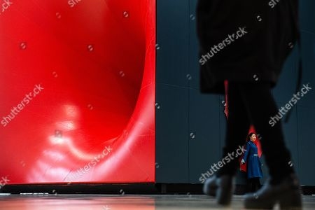 A visitor poses for photos next to 'Sectional Body preparing for Monadic Singularity' artwork during an exhibition of British-Indian artist Anish Kapoor, at the CAFA Art Museum in Beijing, China, 19 November 2019. The first solo museum show in China for Anish Kapoor presents his most significant works and runs until 01 January 2020.
