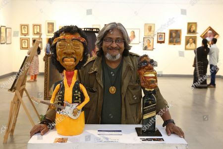 Indian Caricature Sculpture clay artist Umesh Prasad pose with his art work  James. Marshall ?Jimi? Hendrix Legendary American Rock guitarist, singer and song writer (L) and Ray Charles Robinson was an American blind singer, song writer, musician and composer (R) portrait and figurative art  themed ?Celebrations of Human Art? exhibition at Chitra kala Parishad in Bangalore, India 19 November 2019.Around 34 artists from different parts of karnataka exhibit their collective artwork of celebrities and portraying the different moods, emotions, happiness and taught?s of an human being in their daily life.