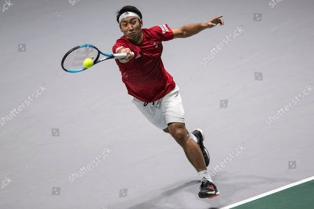 Japan's Yasutaka Uchiyama returns the ball to France's Jo-Wilfried Tsonga during their Davis Cup tennis match in Madrid, Spain