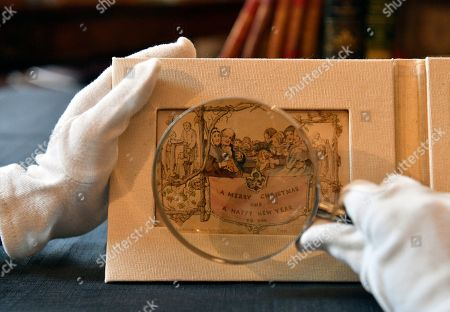 """Stock Image of The world's first printed Christmas card is displayed at the Dickens House Museum in Lon?don, Britain, 19 November 2019. The hand coloured lithograph card was produced in 1843 and sold for one shilling. The exhibition """"Dickens and the Business of Christmas"""" opens 20 November 2019 until 19 April 2020"""