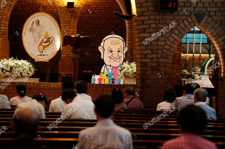 People pray at the Assumption Cathedral as a caricature of Pope Francis is placed alongside in Bangkok, Thailand, . Pope Francis arrives in Thailand on Wednesday for the first visit here by the head of the Roman Catholic Church since St. John Paul II in 1984