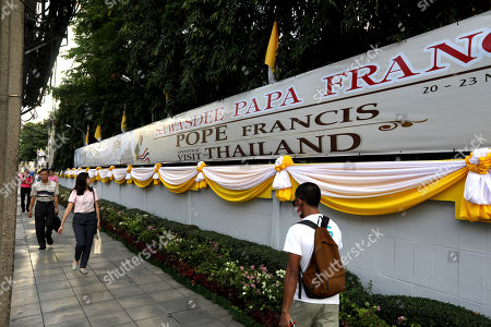 People walk past a banner welcoming Pope Francis in Bangkok, Thailand, . Pope Francis arrives in Thailand on Wednesday for the first visit here by the head of the Roman Catholic Church since St. John Paul II in 1984