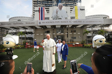 Nurses of St.Louis hospital get themselves photographed with a life size statue of Pope Francis in Bangkok, Thailand, . Pope Francis arrives in Thailand on Wednesday for the first visit here by the head of the Roman Catholic Church since St. John Paul II in 1984