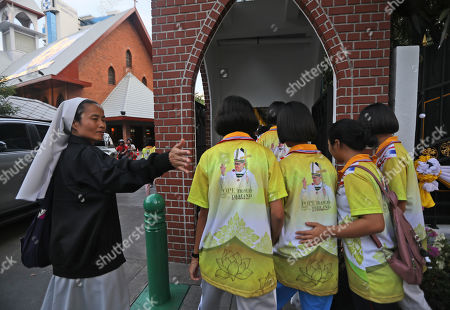 A nun guides her students wearing Pope Francis t-shirt inside a convent in Bangkok, Thailand, . Pope Francis arrives in Thailand on Wednesday for the first visit here by the head of the Roman Catholic Church since St. John Paul II in 1984
