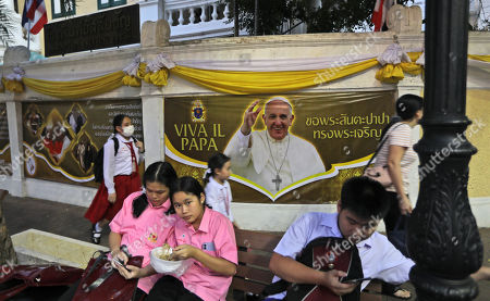 Students wait for transportation next to a poster of Pope Francis in Bangkok, Thailand, . Pope Francis arrives in Thailand on Wednesday for the first visit here by the head of the Roman Catholic Church since St. John Paul II in 1984