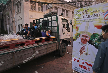 Workers drive past a Pope Francis poster placed at the entrance of Assumption cathedral in Bangkok, Thailand, . Pope Francis arrives in Thailand on Wednesday for the first visit here by the head of the Roman Catholic Church since St. John Paul II in 1984