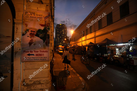A girl walks past Pope Francis poster pasted on a wall near Assumption cathedral in Bangkok, Thailand, . Pope Francis arrives in Thailand on Wednesday for the first visit here by the head of the Roman Catholic Church since St. John Paul II in 1984