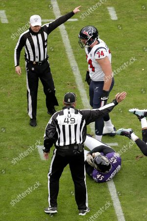 NFL referee Alex Kemp, top left, and umpire Rich Hall (49) gestures after Baltimore Ravens linebacker Jaylon Ferguson (45) recovered a fumble from Houston Texans quarterback Deshaun Watson, not visible, during the first half of an NFL football game, in Baltimore