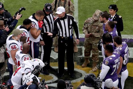 NFL referee Alex Kemp, top in white hat, shows the coin to Houston Texans linebacker Dylan Cole (51) before the coin flip at midfield prior to an NFL football game between the Baltimore Ravens and the Houston Texans, in Baltimore