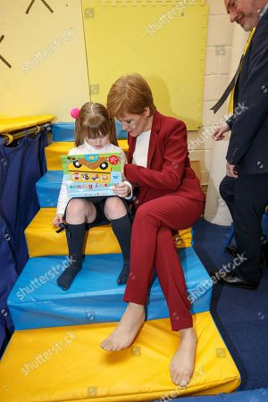 Scottish First Minister and SNP leader  Nicola Sturgeon (R) reads with a child, at the bOunceT Children's activity class, during a campaign trail with Alyn Smith (R), the SNP's candidate for Stirling, in Stirling, Britain, 19 November 2019. British Prime Minister Boris Johnson has called a general election for 12 December 2019.