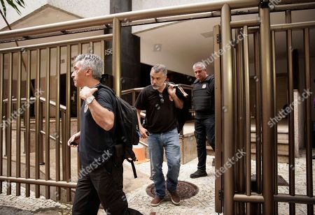 Federal police officers leave a residential building carrying seized documents from suspects under investigation for kickbacks and money laundering, in Rio de Janeiro, Brazil, . Brazilian police are seeking the arrest of Paraguay's ex-President Horacio Cartes as part of the investigation