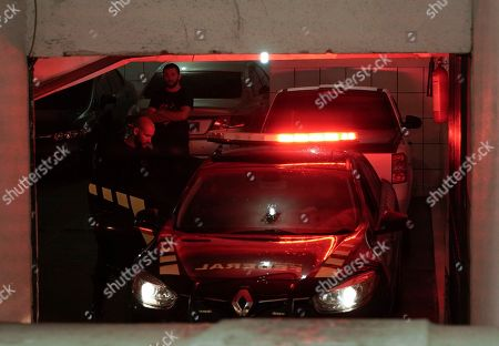 Federal police officers stand in a residential building garage in Rio de Janeiro, Brazil, . Brazilian police are seeking the arrest of several people, including Paraguay's ex-President Horacio Cartes, as part of a massive investigation into kickbacks and money laundering