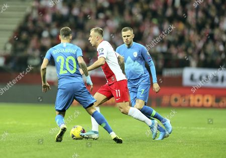 Poland's Kamil Grosicki (C) and Slovenia's Petar Stojanovic (L) and Josip Ilicic (P) in action during the UEFA EURO 2020 group G qualifying soccer match between Poland and Slovenia at PGE National stadium in Warsaw, Poland, 19 November 2019. Poland won 3-2.