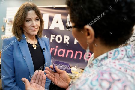Democratic presidential candidate and author Marianne Williamson talks to a supporter during an election stop at the Next Millennium Books & Gifts store in Omaha, Neb