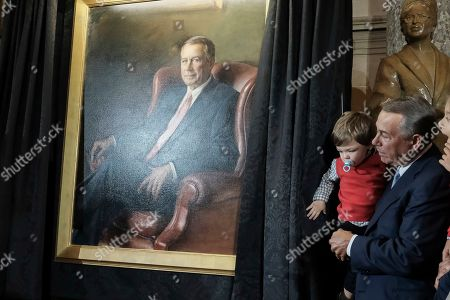 Former Speaker of the House John Boehner, holds his grandson as he unveils a portrait of himself on Capitol Hill, in Washington