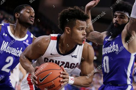 Stock Image of Gonzaga guard Admon Gilder, center, prepares to pass the ball while pressured by Texas-Arlington forward Jordan Phillips, left, and guard Brian Warren during the second half of an NCAA college basketball game in Spokane, Wash., . Gonzaga won 72-66