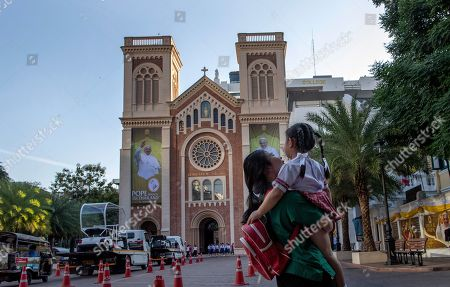 A woman carries a child across Assumption Cathedral courtyard, decorated with posters of Pope Francis in Bangkok, Thailand, . Pope Francis arrives in Thailand on Wednesday for the first visit here by the head of the Roman Catholic Church since St. John Paul II in 1984
