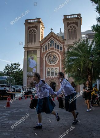 School children run in the courtyard of Assumption Cathedral, decorated with posters of Pope Francis in Bangkok, Thailand, . Pope Francis arrives in Thailand on Wednesday for the first visit here by the head of the Roman Catholic Church since St. John Paul II in 1984