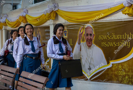 School children walk in Assumption Cathedral courtyard, decorated with posters of Pope Francis in Bangkok, Thailand, . Pope Francis arrives in Thailand on Wednesday for the first visit here by the head of the Roman Catholic Church since St. John Paul II in 1984