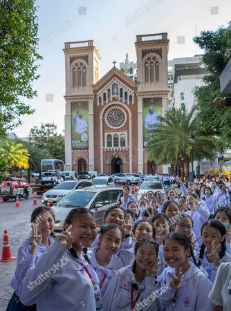 School children pose for a photo as they walk in Assumption Cathedral courtyard, decorated with posters of Pope Francis in Bangkok, Thailand, . Pope Francis arrives in Thailand on Wednesday for the first visit here by the head of the Roman Catholic Church since St. John Paul II in 1984