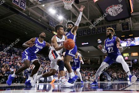 Gonzaga guard Admon Gilder, second from the left, passes the ball while pressured by Texas-Arlington forward Jordan Phillips, left, guard Brian Warren, second from the right, and forward TiAndre Jackson-Young during the second half of an NCAA college basketball game in Spokane, Wash