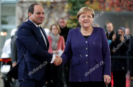 Egypt's President Abdel Fattah al-Sisi, left, and German Chancellor Angela Merkel, right, shake hands prior to a bilateral meeting as part of the 'Compact with Africa' conference in Berlin, Germany