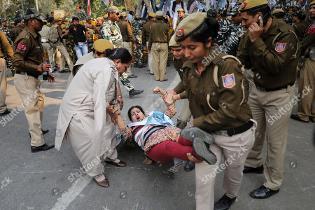 Delhi police officers detain a Congress party supporter during a protest against the withdrawal of Special Protection Group (SPG) cover to party president Sonia Gandhi, her children Rahul Gandhi and Priyanka Vadra and former prime minister Manmohan Singh, in New Delhi, India, . The move to lift off the SPG security, an elite force that protects prime ministers and their immediate families, led to sharp reactions from the Congress, which accused the government of personal vendetta
