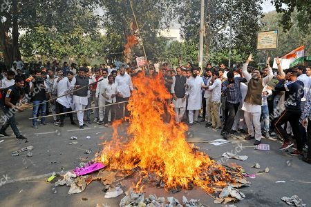 Congress party supporters burn effigies of Indian prime minister Narendra Modi and home minister Amit Shah during a protest against the withdrawal of Special Protection Group (SPG) cover to party president Sonia Gandhi, her children Rahul Gandhi and Priyanka Vadra and former prime minister Manmohan Singh, in New Delhi, India, . The move to lift off the SPG security, an elite force that protects prime ministers and their immediate families, led to sharp reactions from the Congress, which accused the government of personal vendetta