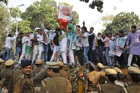 Congress party supporters shout slogans as they hold a severed head of an effigy of Indian prime minister Narendra Modi while standing on a police barricade during a protest against the withdrawal of Special Protection Group (SPG) cover to party president Sonia Gandhi, her children Rahul Gandhi and Priyanka Vadra and former prime minister Manmohan Singh, in New Delhi, India, . The move to lift off the SPG security, an elite force that protects prime ministers and their immediate families, led to sharp reactions from the Congress, which accused the government of personal vendetta
