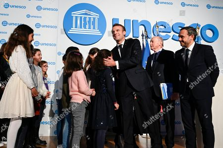 French President Emmanuel Macron (3R) welcomes children next to French Ombudsman (Defenseur des droits) Jacques Toubon (2R) and French junior minister Adrien Taquet (R) during the 30th anniversary of the Convention on the Rights of the Child (UNCRC) at the UNESCO in Paris, France, 20 November 2019.