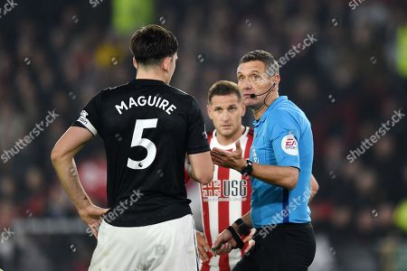 Referee Andre Marriner holds up play whilst VAR is checked.