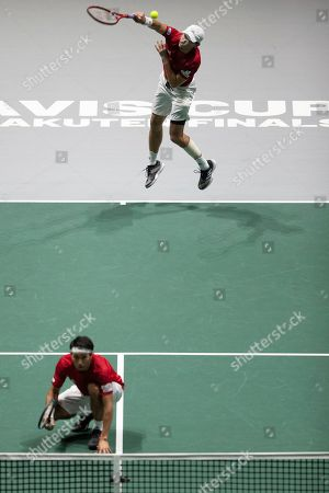 Japan's Ben McLachlan, foreground, and Yasutaka Uchiyama during their Davis Cup tennis double match against Serbia's Janko Tipsarevic and Viktor Troicki in Madrid, Spain