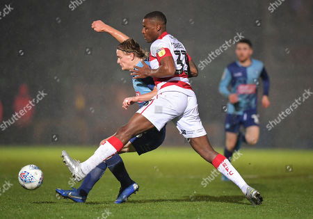 Stock Image of Alex Samuel of Wycombe Wanderers under pressure from Donervon Daniels of Doncaster Rovers